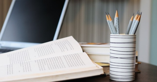 book open and sharpened pencils in a cup