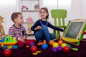 a boy and girl playing with plastic colorful balls